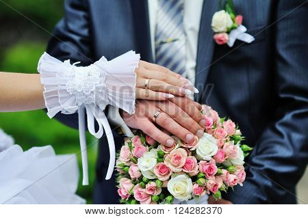 Hands and rings on wedding bouquet bride and groom