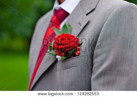 Red boutonniere on gray groom's jacket outdoor