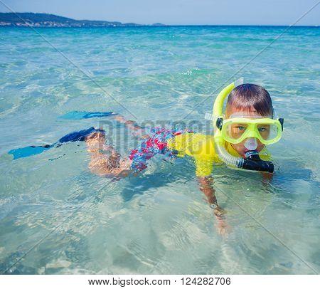 Joyful boy scuba diving in the clear sea.