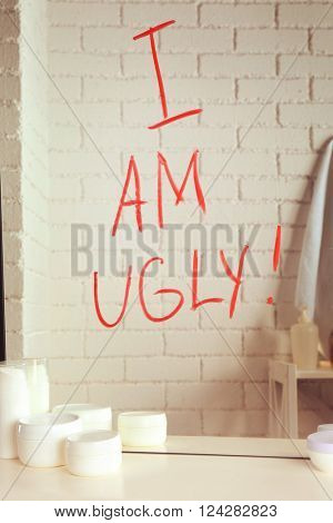 Text I AM UGLY written on mirror in the bathroom