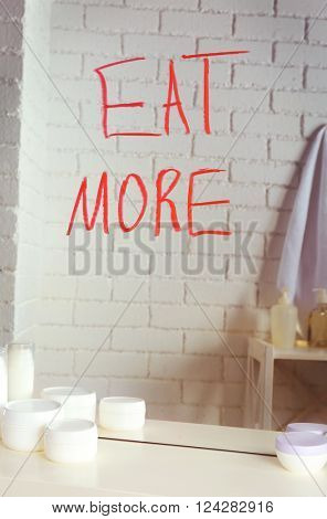 Text EAT MORE written on mirror in the bathroom
