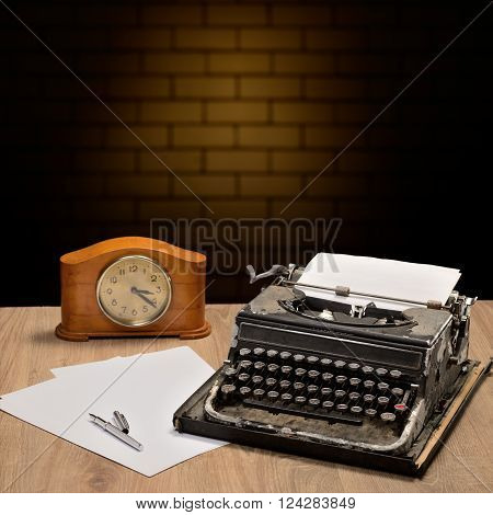 Vintage typewriter and blank sheets of paper on wooden table. Brick wall behind