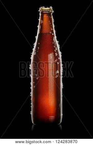 Cold brown bottle of beer with water droplets and ice over black background