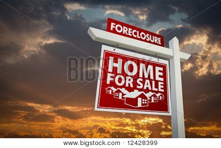 Red Foreclosure Home For Sale Real Estate Sign Over Beautiful Clouds and Sunset Sky.