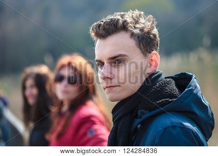Closeup of a teenage boy with his family in the background