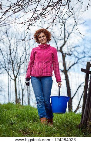 Full length of a farmer woman in her garden holding a blue bucket