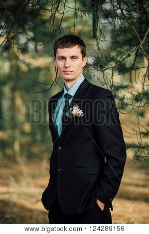 Close Up Portrait Of Handsome Stylish Groom Outdoors In Park With Red Bowtie