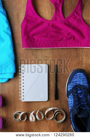 Athlete's set with female clothing, tape centimeter and notebook on wooden background