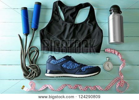 Athlete's set with female clothing, equipment and bottle of water on blue wooden background