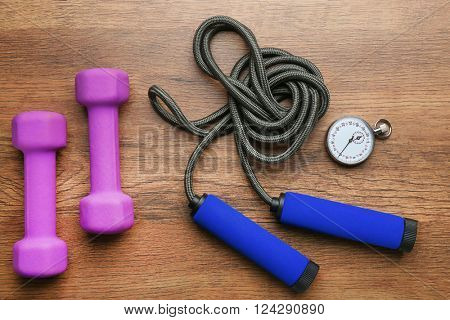 Athlete's set with stopwatch, dumbbells and skipping rope on wooden background