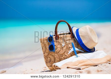 Beach accessories - bag, straw hat, sunglasses on white beach