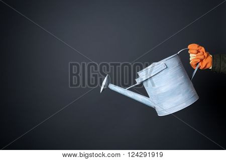 Hand holding metal watering can on grey background