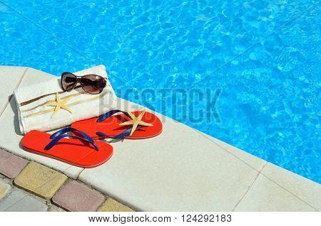 Flip-flops sunglasses towel starfish on the swimming pool.