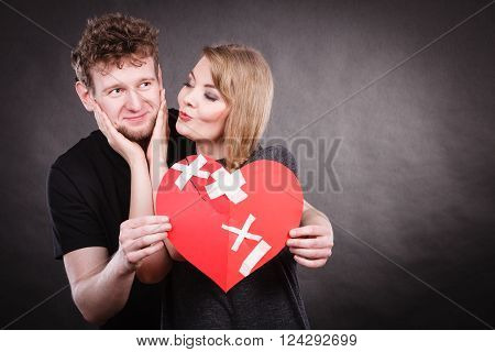 Heal love concept. Couple woman and man holding two halves of broken heart fixed with plaster bandage going to be joined in one.