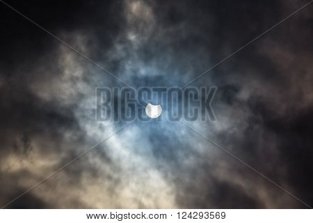 Picturesque cloudy sky with partial solar eclipse
