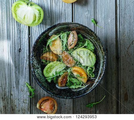 Salad with arugula, heirloom tomatoes and parmesan on wood background.