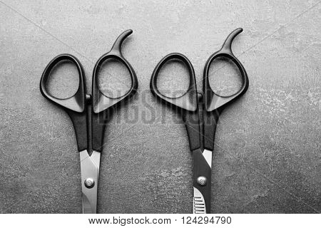 Professional scissors with black handles on a dark grey surface, top view