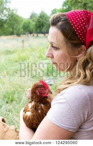 A peasant woman with a chicken on her arm gazing dreamily into the distance