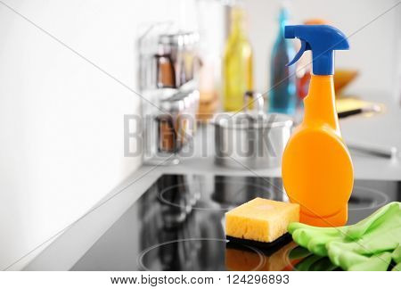 Detergent with protective gloves and sponge on electric hob in the kitchen
