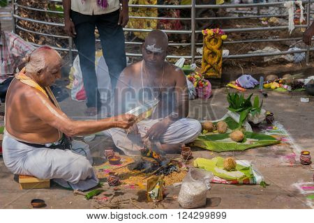 Trichy India - October 15 2013: Half-naked older guru performs religious ritual in front of client both sitting in mandala. He channels the smoke of the fire with offerings. Half-naked client has forehead smeared white.