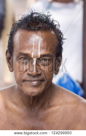 Trichy India - October 15 2013: Closeup of man's face with white Vishnu symbol on his forehead painted by guru at Amma Mandapam. This is part of a religious ritual performed by guru.