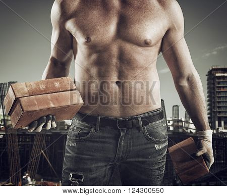 Sexy dirty bricklayer with brick in hand