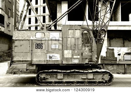 BAKU, AZERBAIJAN - APRIL 07 2014  Old crane in front of construction site. An ancient steel crane shown parked by a modern construction