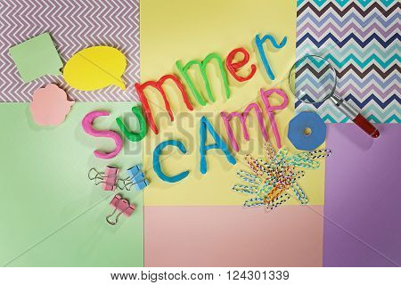 Inscription SUMMER CAMP made of colorful plasticine and stationery on sheets of paper background