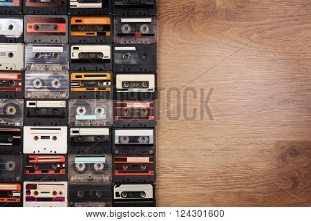 Collection of audio cassettes on wooden table background