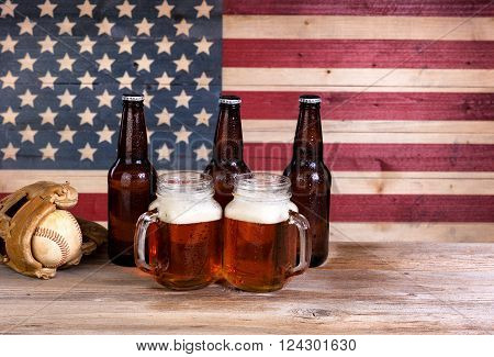 Two pint jars filled with beer full bottles and baseball mitt with vintage wooden USA flag in background.
