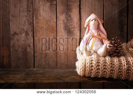 Toy bunny with woolen scarf on wooden background