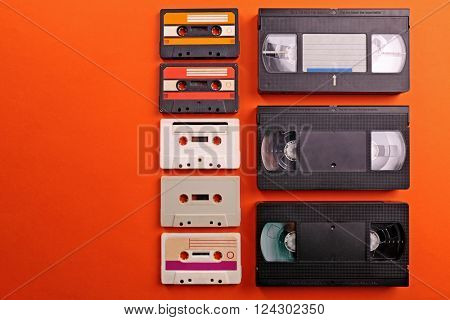 Set of old audio and video cassettes on red background