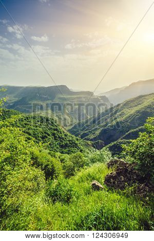 Beautiful landscape with green mountains and magnificent cloudy sky in sunset