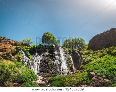 View of beautiful mountain waterfall with blue sky on background
