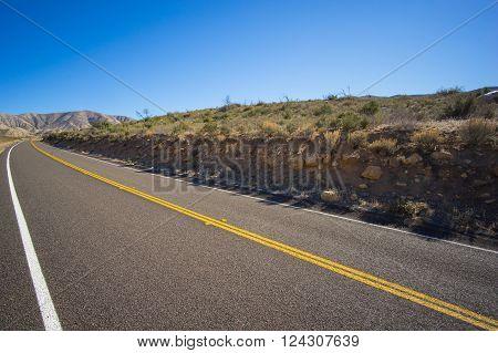 Road cuts into desert hillside in the barren mojave desert.