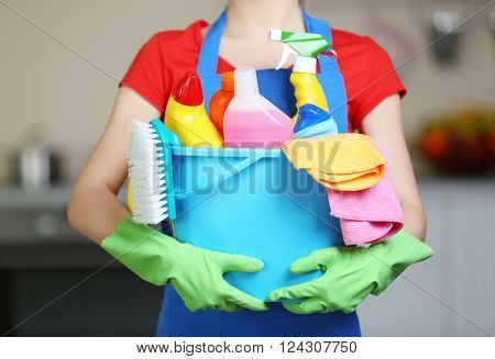 Cleaning concept. Young woman holds basin with washing fluids and rags in hands, close up