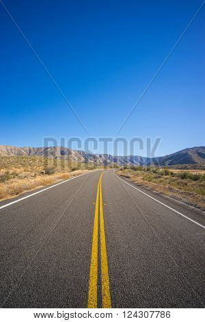Long straight road leading through the Mojave desert of southern California.