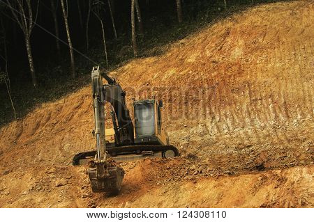 heavy road construction machine working on hill