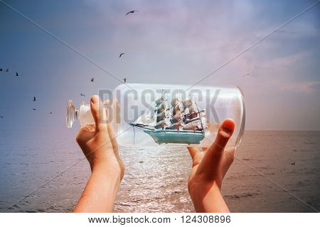 Textured image of a child holding a ship in a bottle at the ocean