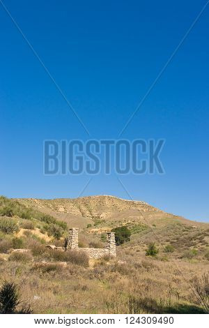 Ruins of a stone porch from destroyed ranch house in southern California hills.