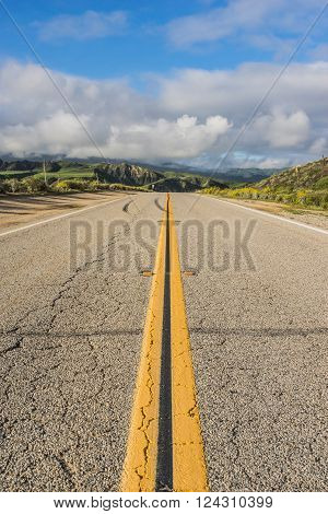 Straight road of asphalt drives forward into the green hills of southern California.