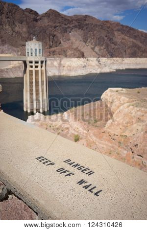 Sign warning of the danger of standing on the wall above the Hoover Dam.