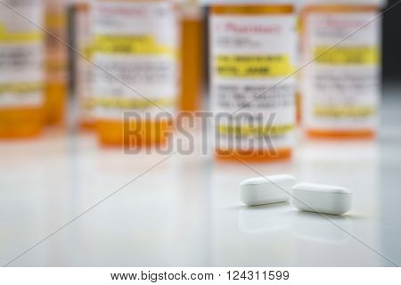 Variety of Non-Proprietary Medicine Bottles and Large Pills on Reflective Surface With Grey Background.
