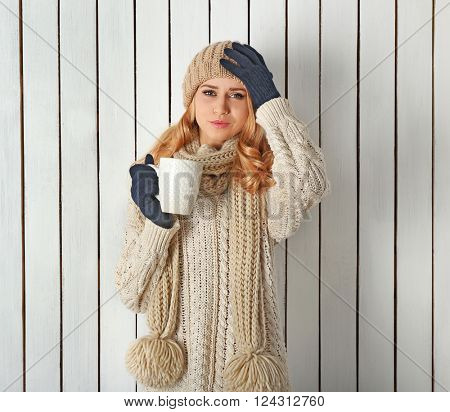 Winter portrait of young beautiful blond woman in her knitted warm clothing, with cup of hot drink