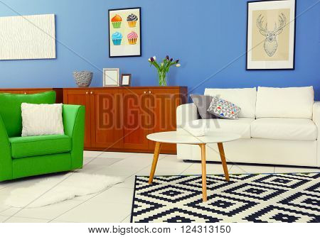 Modern living room interior with white sofa, coffee table, big graphic carpet, green chair and canvases on the blue wall