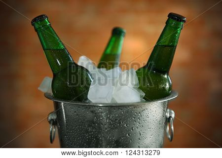 Green glass bottles of beer in ice-pail, close up