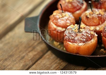 Baked apples with cottage cheese, raisins and walnut in pan on wooden table