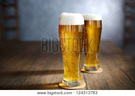 Two glasses of light beer on wooden table