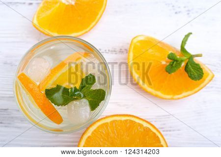 Fresh cocktail with ice, mint and orange on white wooden table background