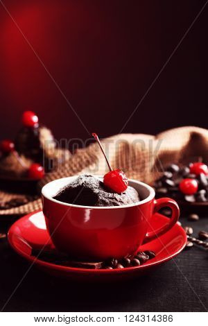 Chocolate cake in a red mug with a cherry on a dark background, close up